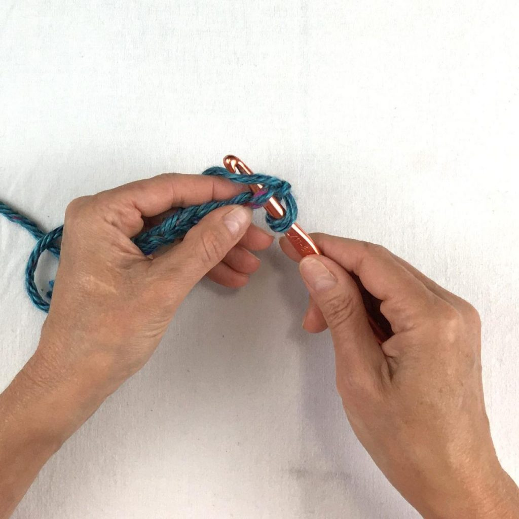 Insert crochet hook in second chain and yarn over